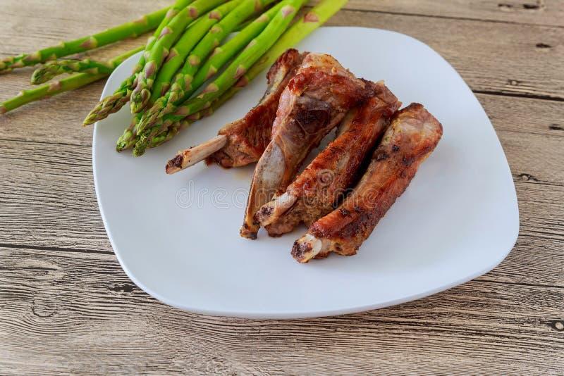 Abendessen von heißen gegrillten Rindfleischfleischrippen diente mit Spargel auf Platte stockfotos