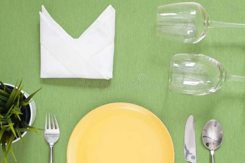 Abendessengedeck eine gelbe Platte mit silberner Gabel und Löffel O lizenzfreie stockfotografie