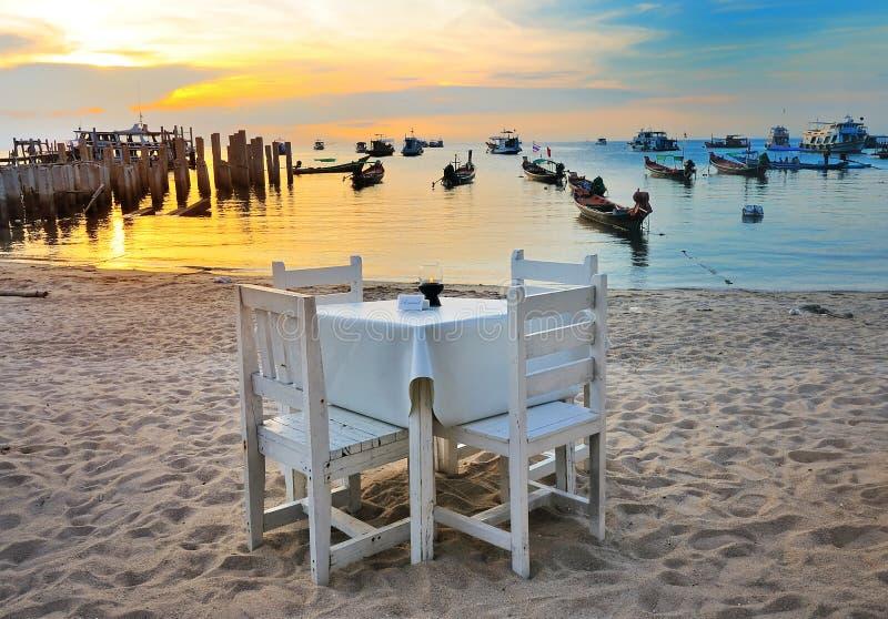 Abendtisch auf dem Strand auf Sonnenuntergangzeit lizenzfreie stockfotos