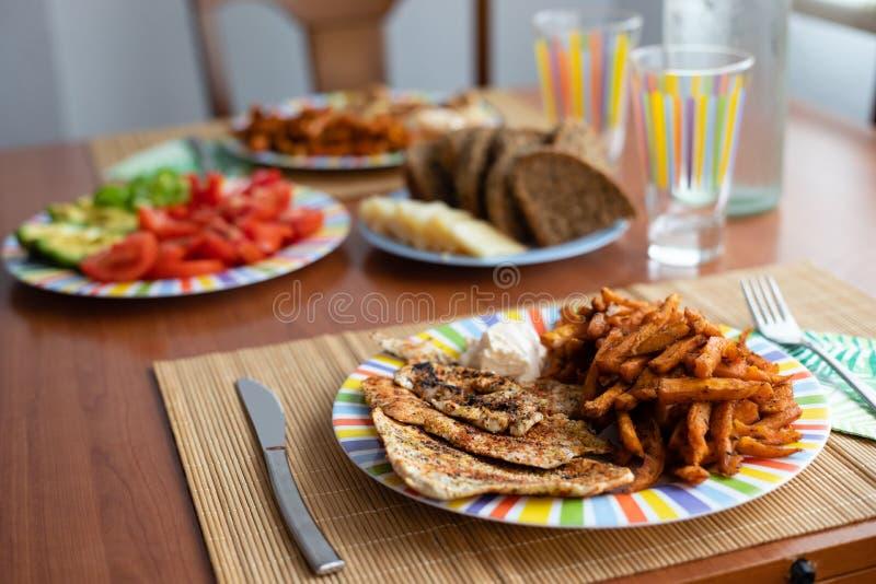 Abendtisch mit Salatteller, Huhn, Süßkartoffeln, Brot und buntem Wasserglas stockfotografie