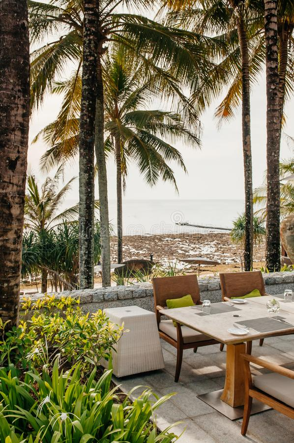 Abendtisch und Stühle unter Regenschirm im tropischen Kokosnussbaum stockfoto