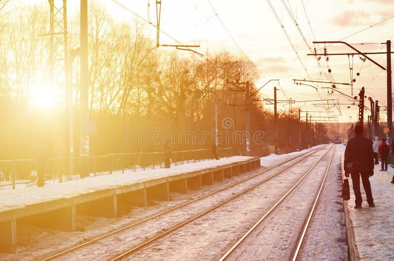 Abendwinterlandschaft mit dem Bahnhof Schneebedeckte Bahnplattform unter dem Sonnenlicht bei Sonnenuntergang Ein Platz wo peo stockfoto