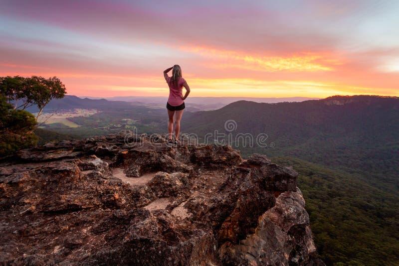 Abenteuerliche Frau, die den Sonnenuntergang nach einem langen Tag wandert in den blauen Bergen aufpasst stockbild