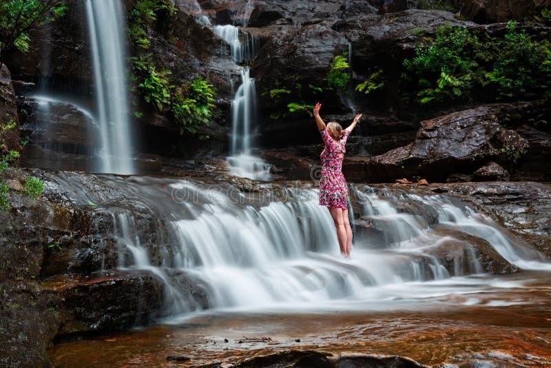 Abenteuerliche weibliche Stellung in den Wasserfällen stockfotografie