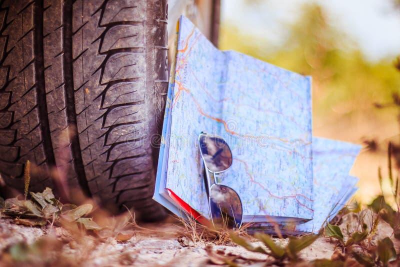 Abenteuerreise: Abschluss des Autoreifens, der Sonnenbrille und der Straßenkarte stockfotos