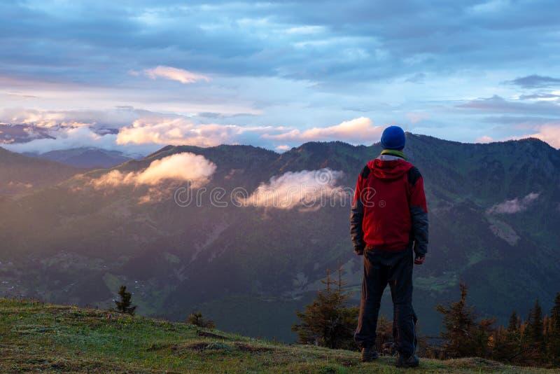 Abenteurer bewundert Sonnenuntergang in den Bergen nach Sturm lizenzfreie stockfotografie