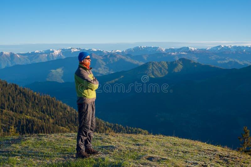 Abenteurer, der den erstaunlichen Bergblick bewundert stockfotografie