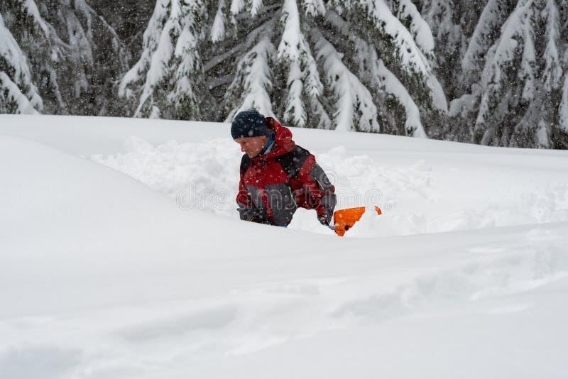 Abenteurer gräbt eine Höhle im Schnee während Schneefälle lizenzfreie stockfotografie