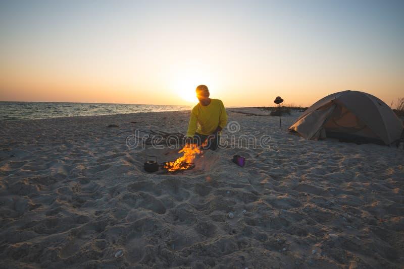 Abenteurer sitzt nahe bei brennendem Feuer auf dem Strand lizenzfreie stockfotos