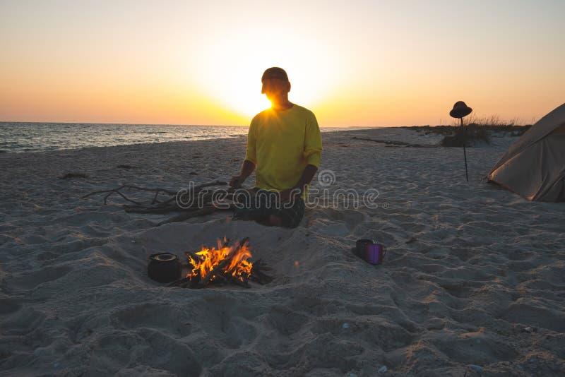 Abenteurer sitzt nahe bei brennendem Feuer auf dem Strand lizenzfreie stockfotografie