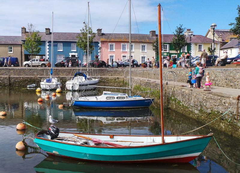 Colourful harbour scene. Aberaeron, United Kingdom - August 10 2013: Four yachts in Aberaeron harbour, in front of a row of colourful houses stock image