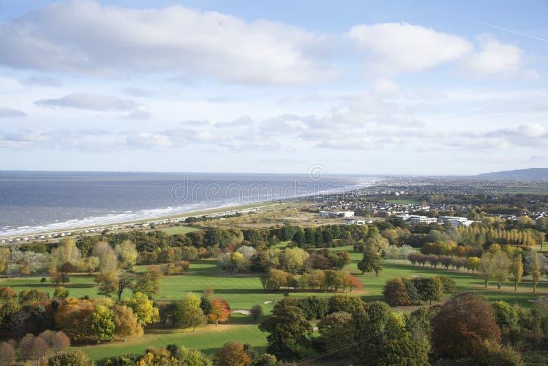 Abergele海岸线,海在显示树、领域和海滩海洋-英国的秋天遇见乡下 库存照片