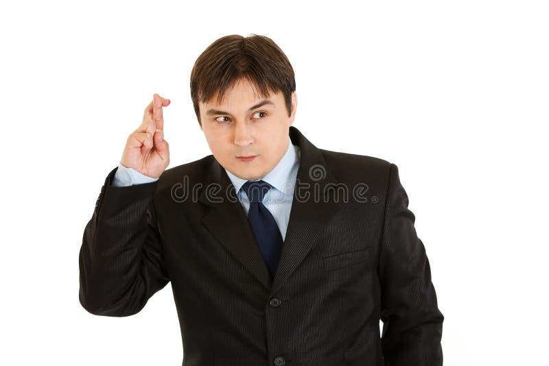 Abergläubische gekreuzte Finger des Geschäftsmannes Holding stockfoto