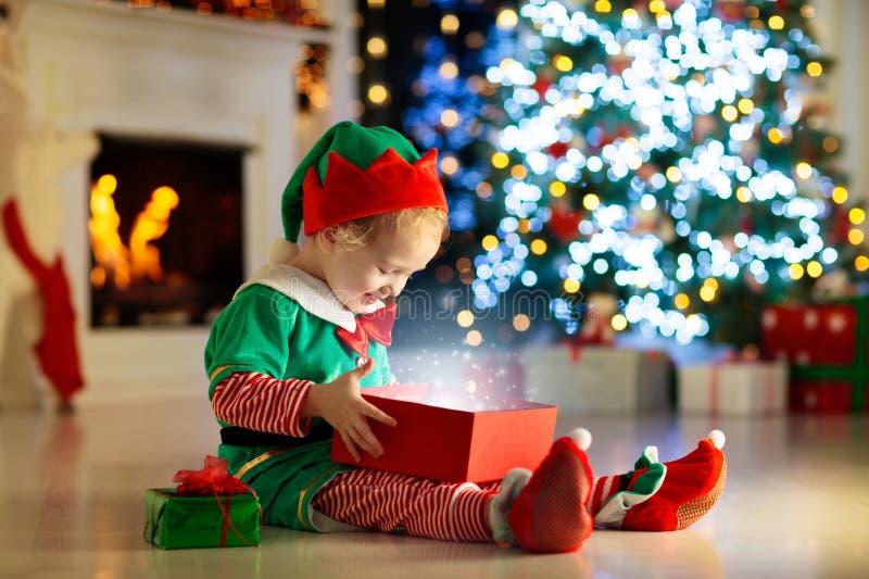 Abertura da criança atual na árvore de Natal em casa Criança no traje do duende com presentes e brinquedos do Xmas  fotografia de stock