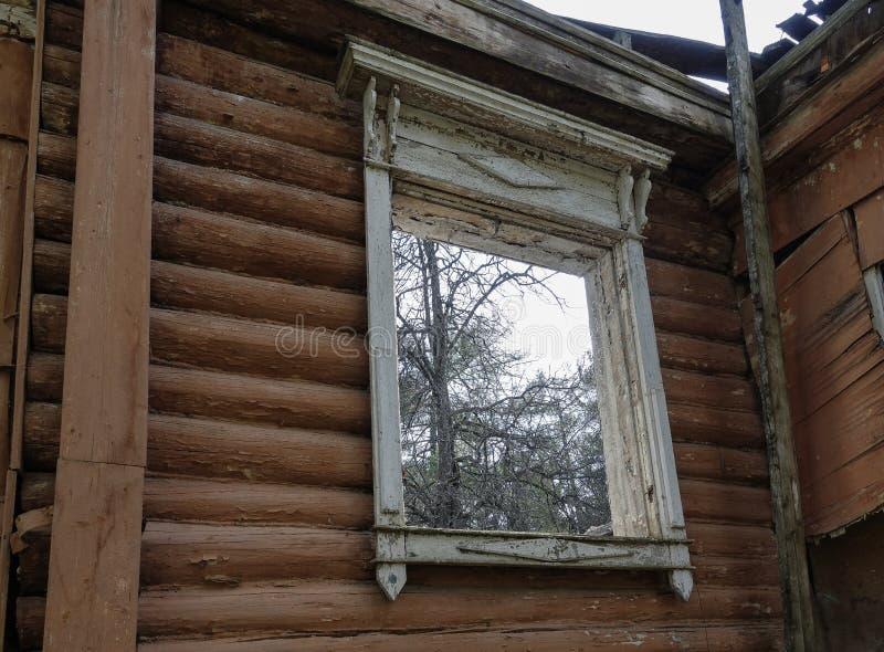 Abertura da janela de uma casa de madeira arruinada velha R?ssia fotografia de stock royalty free
