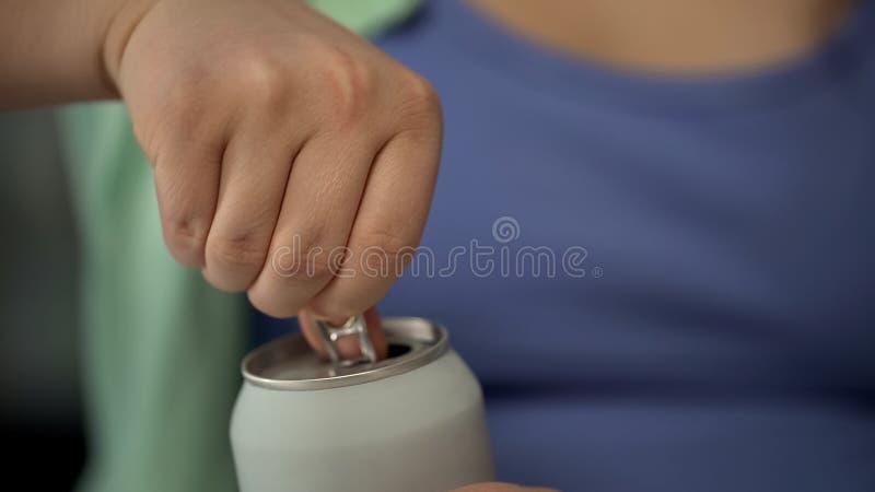 A abertura da senhora pode beber a soda, bebida que contém muito açúcar, close-up fotografia de stock
