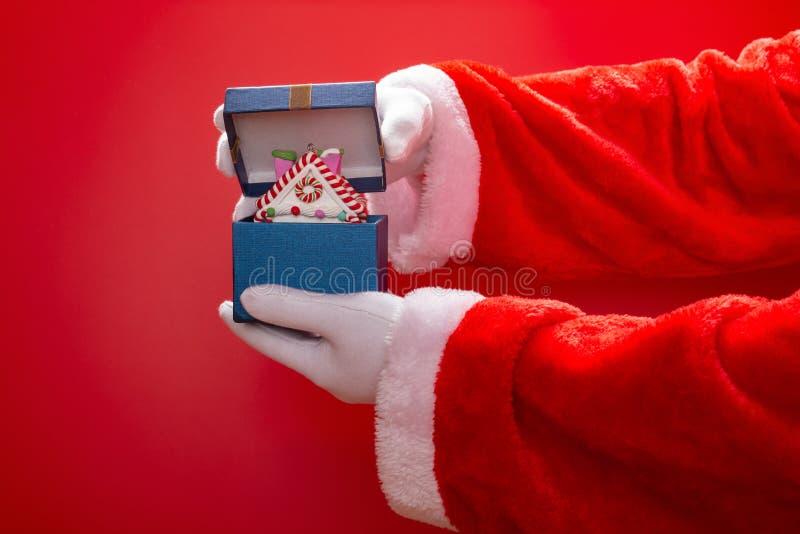 Abertura de Santa Claus una actual caja con el modelo de la casa de la Navidad en rojo foto de archivo libre de regalías