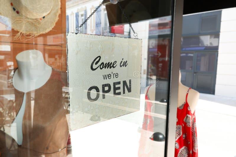 A abertura do negócio com entrada aberta assina dentro a loja da rua através do vidro imagem de stock