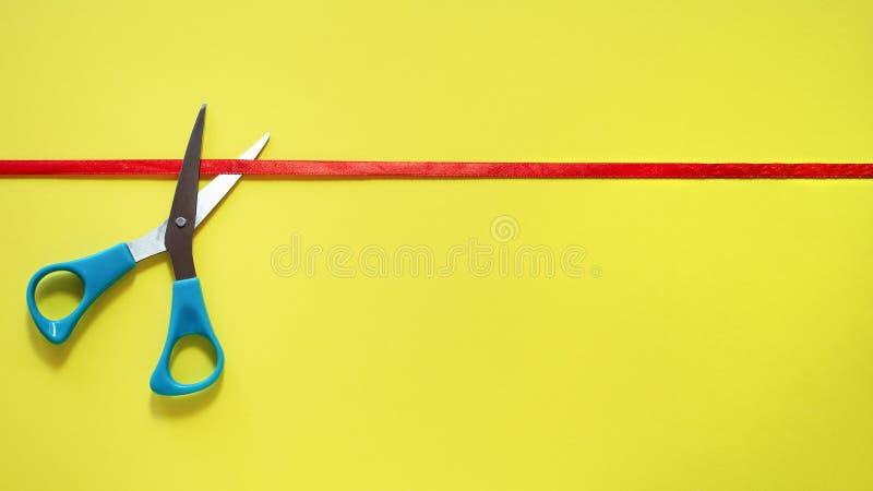 Abertura grande As tesouras cortaram a fita vermelha no fundo amarelo, vista superior ideia da grande inauguração, sinal, símbolo foto de stock