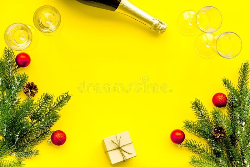 Abeto vermelho, garrafa do champanhe, presente e vidros para a celebração do Natal no modelo amarelo da opinião superior do fundo foto de stock royalty free
