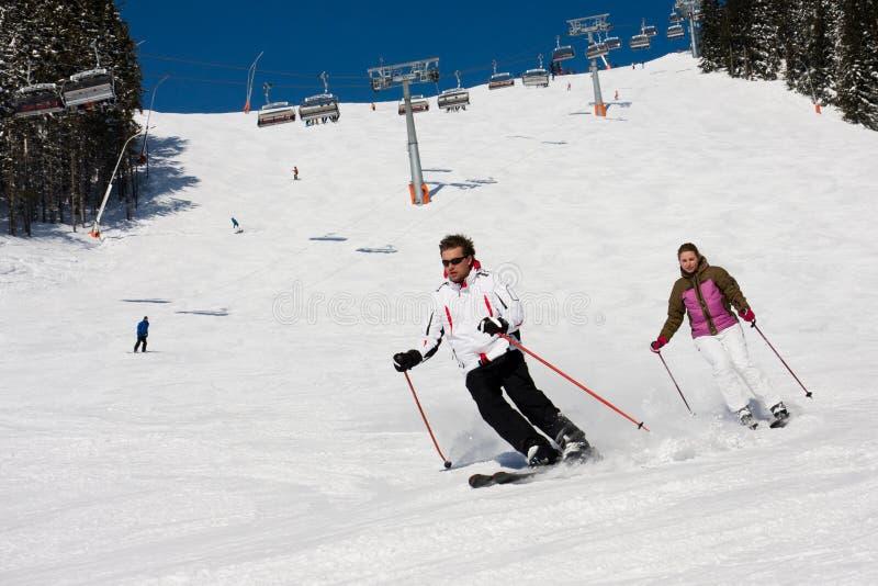 Abfahrtskilauf von zwei Skifahrern lizenzfreies stockfoto