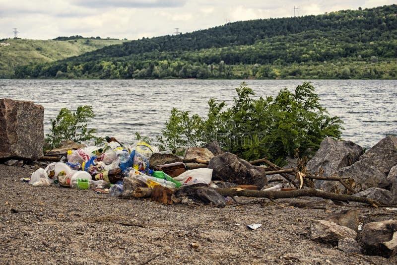 Abfall, Plastik, Flaschen und Plastiktaschen auf der Flussbank stockfotografie