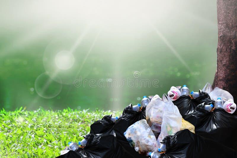 Abfallabfall, Haufen des Abfallplastikabfallschwarzen und Abfalltasche viele am Flussparknaturbaum-Sonnenscheinhintergrund lizenzfreie stockfotos