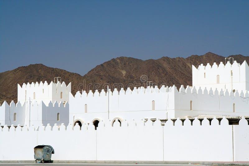 Abfallbehälter vor weißem Haus mit Zinnenwand und unfruchtbarem Gebirgshintergrund, Oman lizenzfreies stockfoto
