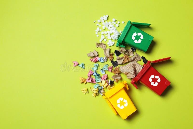 Abfalleimer und unterschiedlicher Abfall auf Farbhintergrund lizenzfreie stockfotos