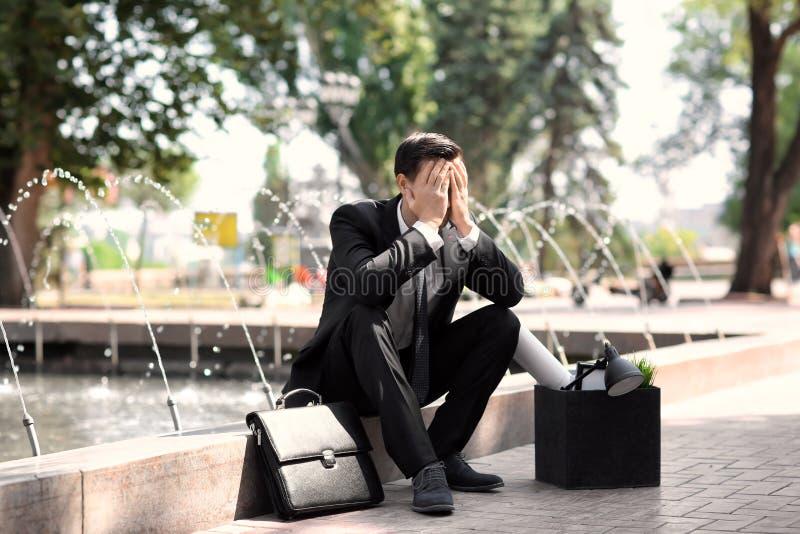Abgefeuertes Büroangestellter mit dem persönlichen Material, das draußen nahe Brunnen sitzt stockfotografie