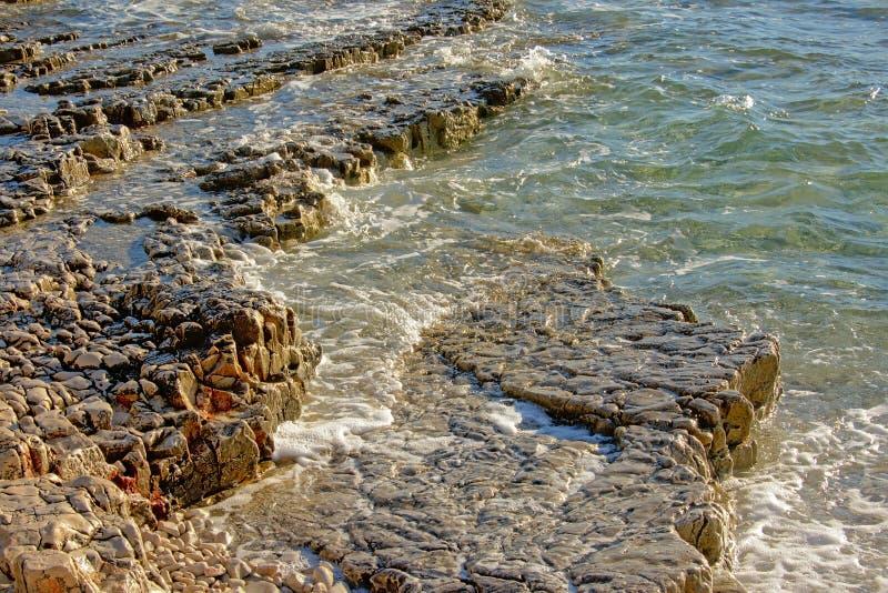 Abgefressene vulkanische Felsen auf der Küste des adriatischen Meeres lizenzfreie stockfotos
