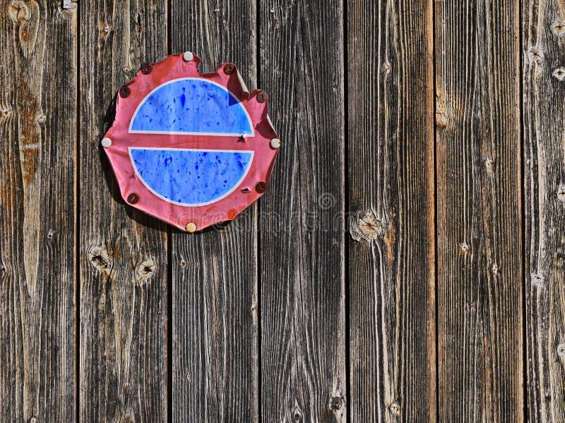 Abgefressenes altes Parkverbotschild auf einer alten hölzernen Wand stockbild