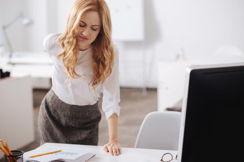 Abgelenkte Gefühlsschmerz der jungen Frau in ihr zurück im Büro stockfoto
