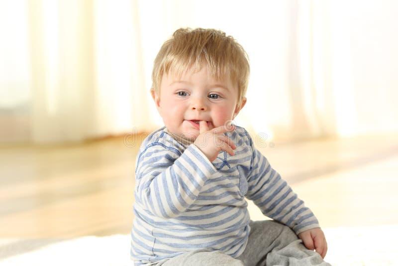 Abgelenktes Kind, das einen Finger sitzt auf dem Boden beißt lizenzfreie stockfotos