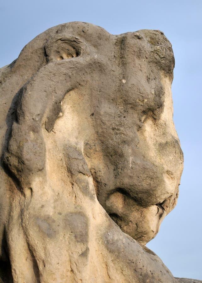 Abgenutzte alte abgefressene Skulptur von Löwen gehen im Profil voran lizenzfreie stockbilder