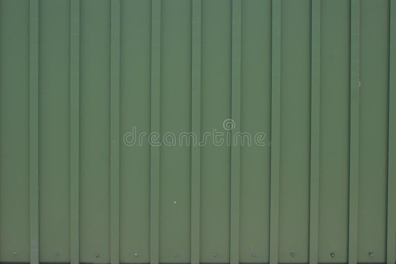 Abgenutzte, gewölbte trapezoide Metallplatten mit Befestigungsbolzen und hellgrünes Pulver beschichten stockfotos