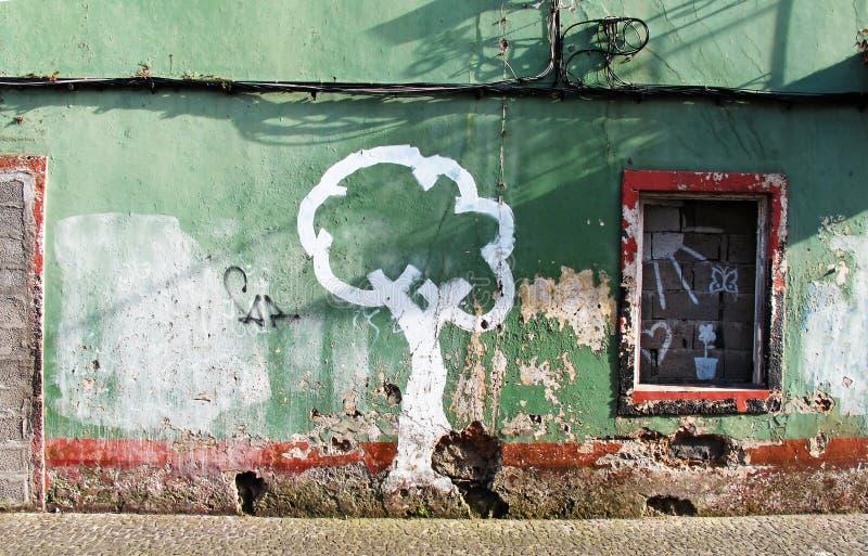 Abgenutzte Häuser im Grün und ein gemalter Baum im Weiß stockfotos