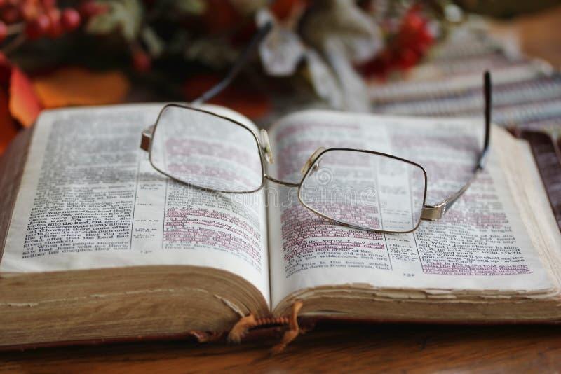Abgenutzte offene Bibel mit Gläsern stockbild