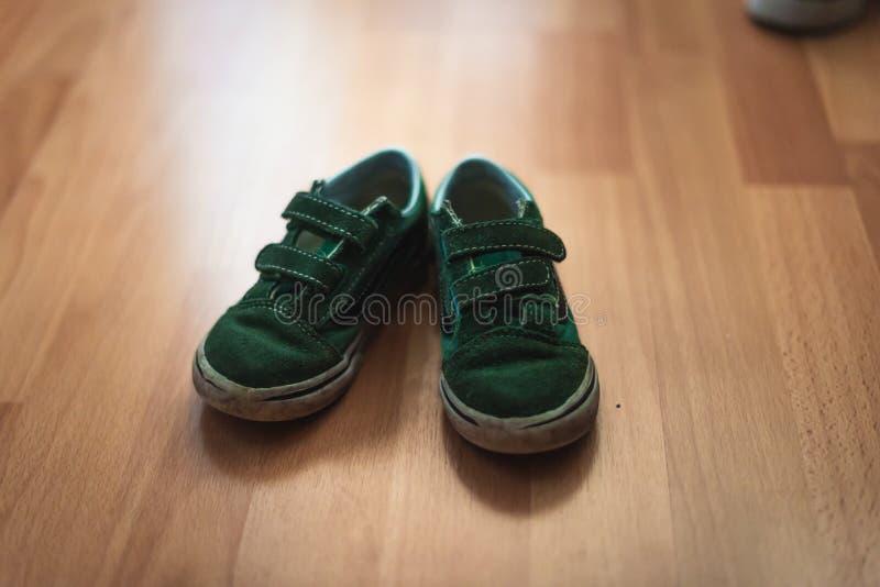 Abgenutzte und schlammige Paare childs Schuhe auf einem Bretterboden eines Wohnzimmers stockfotografie