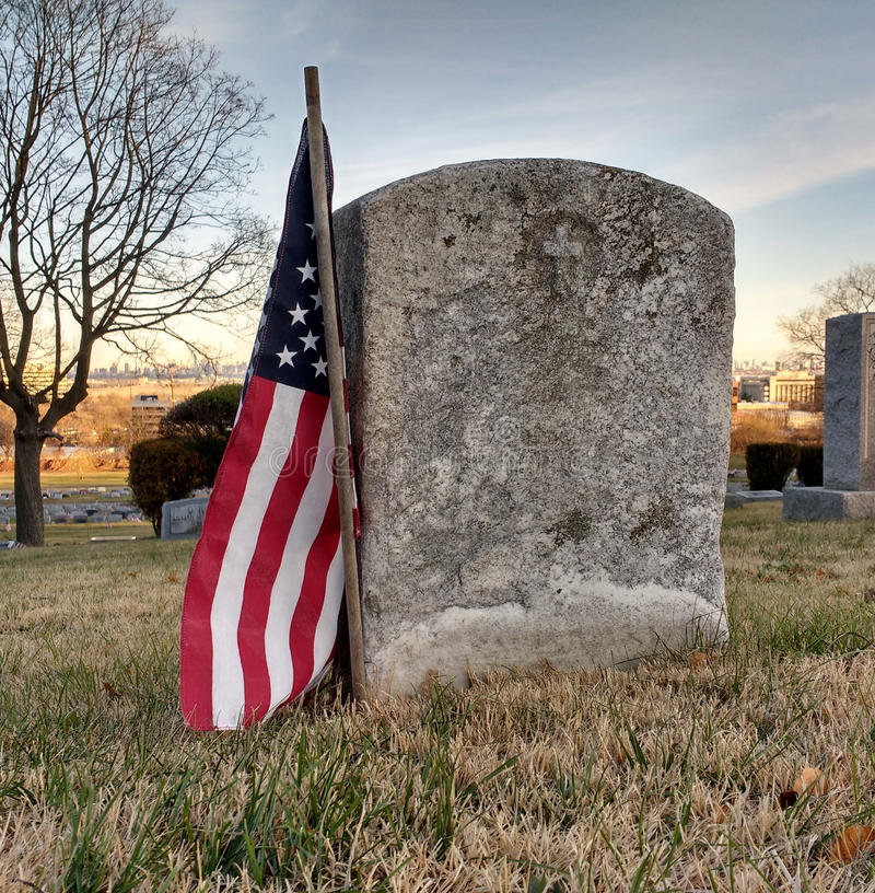 Abgenutzter Grabstein eines Militärveterans geehrt mit einer amerikanischen Flagge lizenzfreie stockfotografie