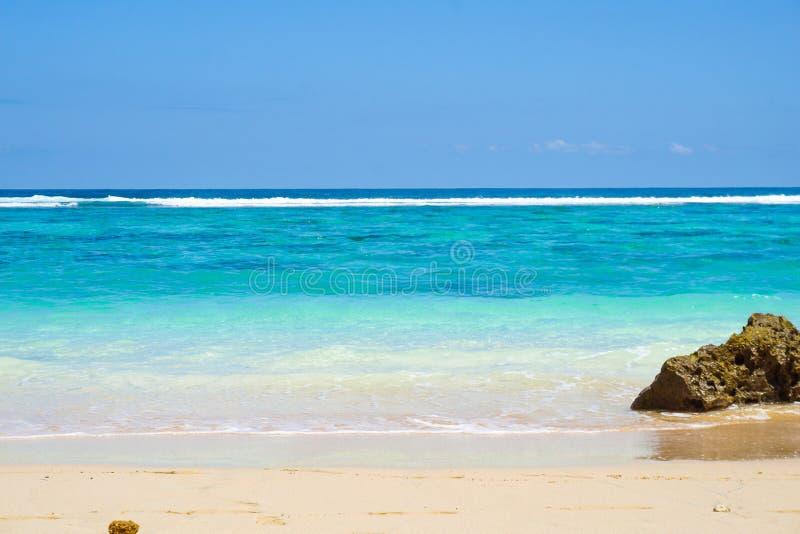 Abgeschlossener goldener sandiger Strand, azurblaues Ozeanwasser stockbild