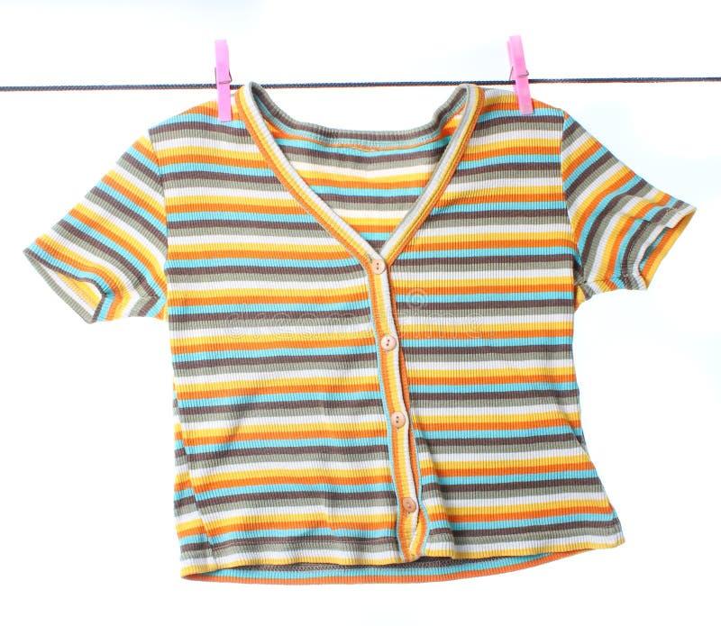 Abgestreiftes T-Shirt, das an einer Wäscheleine mit Schnallen hängt lizenzfreies stockbild
