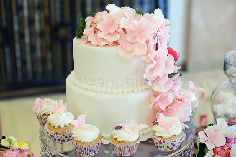Abgestufter Kuchen elegante und einfache zwei bedeckt in der weißen königlichen Zuckerglasur mit rosa dekorativen Blumen und klei stockfoto