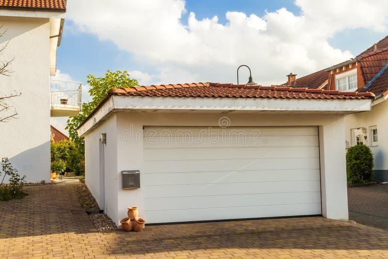 Abgetrennte weiße Garage mit orange Ziegelsteinziegeldach lizenzfreie stockfotografie