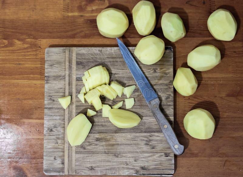 Abgezogene Kartoffeln schnitten †‹â€ ‹auf einem Brett lizenzfreies stockfoto