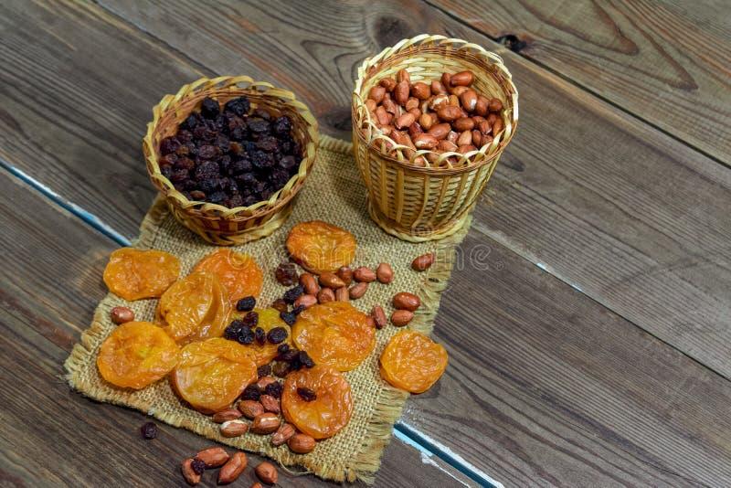 abgezogene rohe Erdnüsse trockneten Aprikosenrosinen auf einem Holztischhintergrund stockfotos