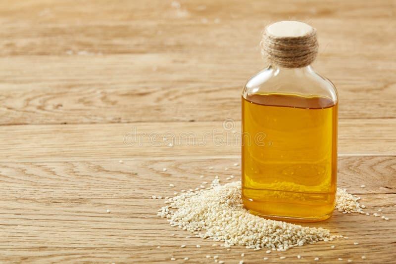 Abgezogene Samen des indischen Sesams mit Öl in einer kleinen Flasche über hölzernem Hintergrund, Nahaufnahme, flache Schärfentie stockfoto