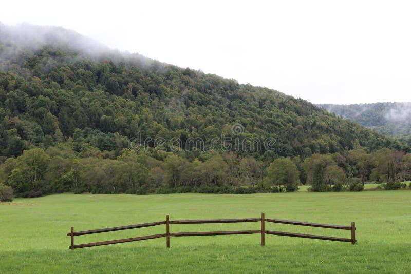 Abhang mit tiefen Wolken und grüne Wiese mit Zaunabschnitt lizenzfreie stockbilder