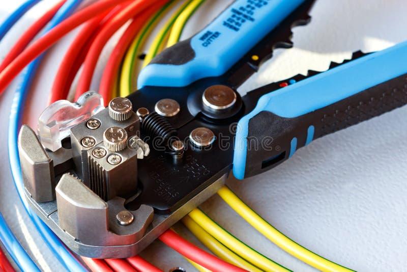 Abisolierzange- und Schnittmeisternahaufnahme mit farbigem Netzanschlusskabel stockbild