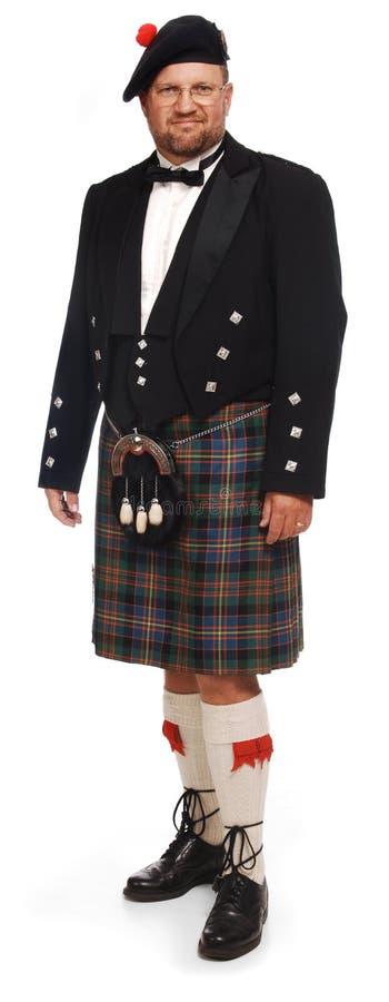Abitante degli altipiani scozzesi in kilt su bianco fotografia stock libera da diritti
